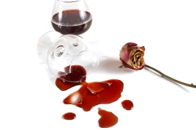 the broken glass with wine and a dry rose